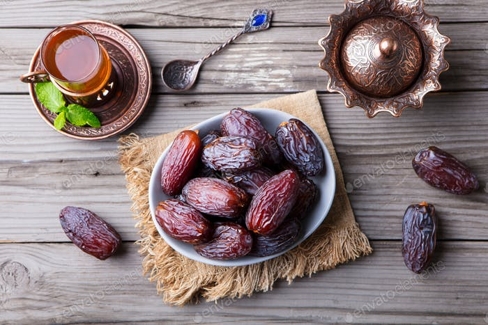 Fresh Medjool Dates in a Bowl with Tea. Ramadan Kareem. Grey Wooden Background.. Top View.