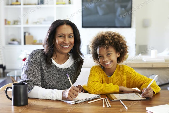 Woman sitting at table in her dining room drawing with her pre-teen granddaughter