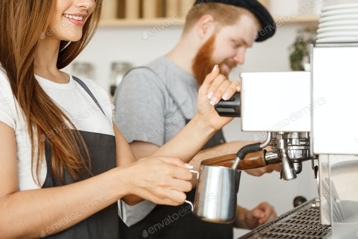 Coffee Business Concept - portrait of lady barista in apron preparing and steaming milk for coffee