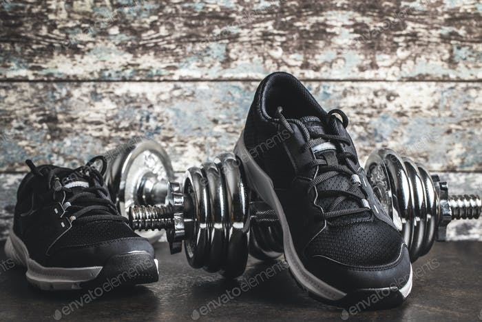 Fitnesskonzept Schwarze Sportschuhe und Kurzhanteln.