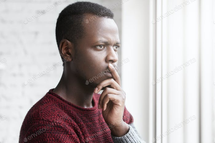 Half profile portrait of handsome young African American writer looking through window with pensive