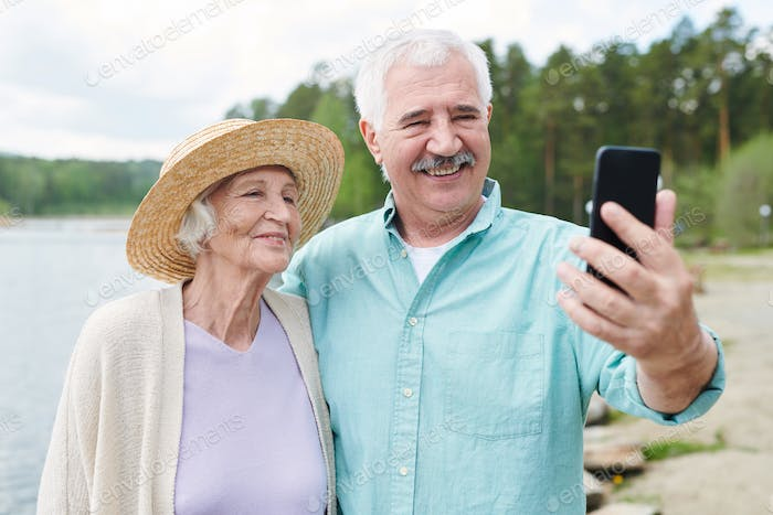 Happy romantic senior couple in casualwear making selfie