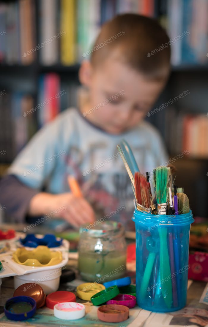Little boy painting pictures at home