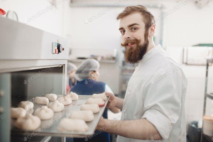 Junge charismatische Bäcker legt ein Backblech mit Brotbrötchen in den Ofen in der Bäckerei