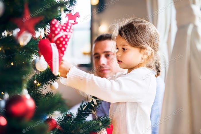 Junger Vater mit Tochter dekoriert Weihnachtsbaum zusammen.