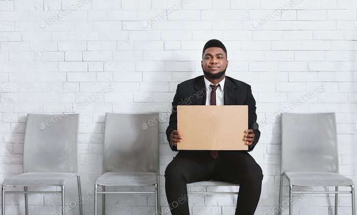 Serious black man in office wear holding blank sign in company hall, waiting for job interview. Copy