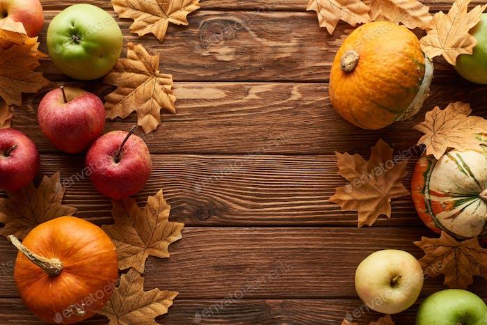 Draufsicht von Kürbissen und Äpfeln auf brauner Holzoberfläche mit getrockneten Herbstblättern
