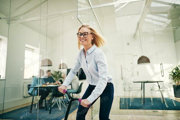 Lächelnd junge Geschäftsfrau Reiten auf einem Roller in einem Büro