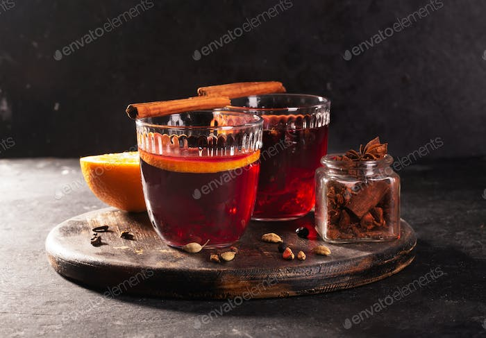 Mulled wine with slice of orange and spices on a wooden background, close up