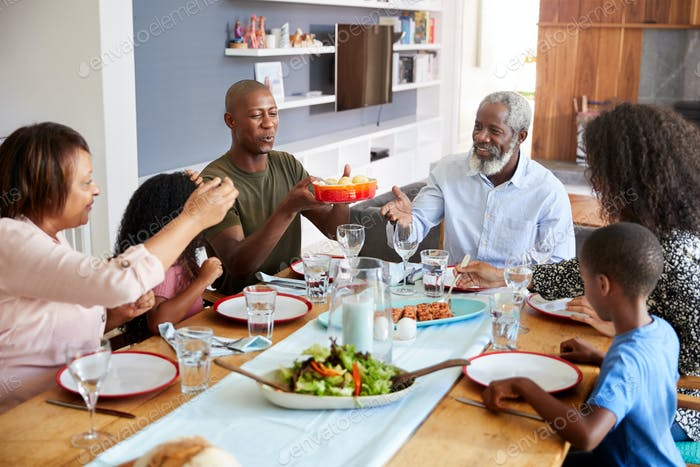 Multi-Generation Family Sitting Around Table At Home Enjoying Meal Together