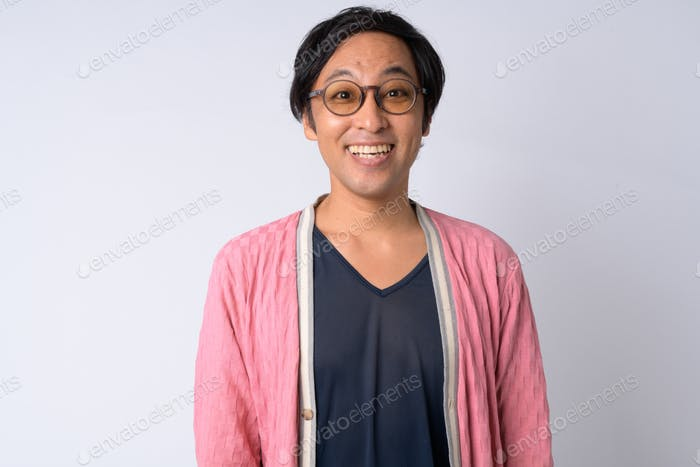 Portrait of happy Japanese man smiling against white background