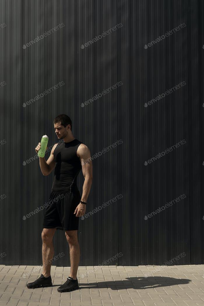 Porträt muskulösen Mann eine Pause, um seinen Körper zu hydratisieren nach