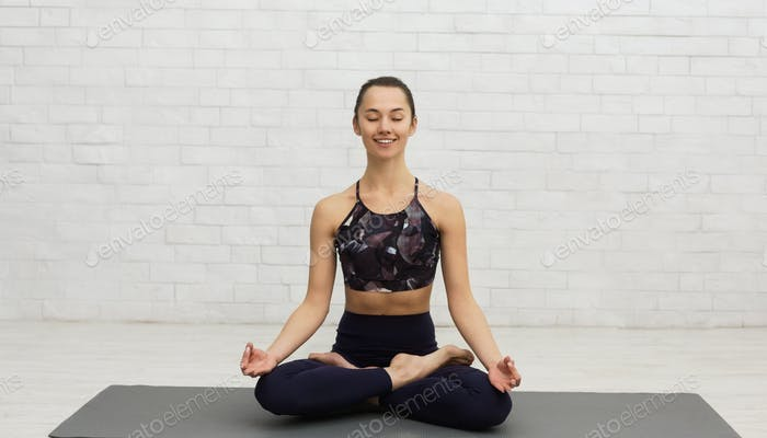 Calm young woman meditating in lotus pose with closed eyes