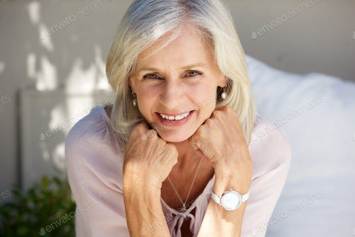smiling older woman with hand in hands outside