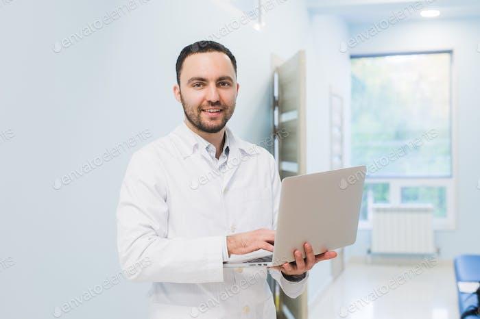 Porträt von Doktor halten Laptop, drinnen