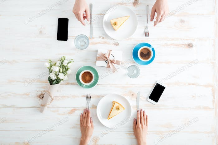 Hands of couple eating cakes and drinking coffee on table