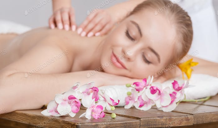Pleasure of spa treatments. Female hands do relaxing massage for woman with closed eyes