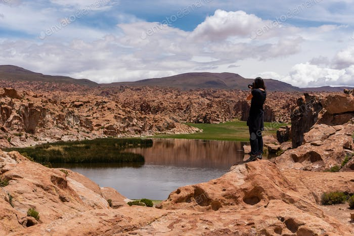 Woman taking a photo of a scenic landscape in the southwest of the Bolivian altiplano