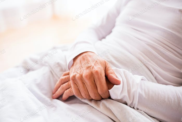 Senior man lying in bed at home.