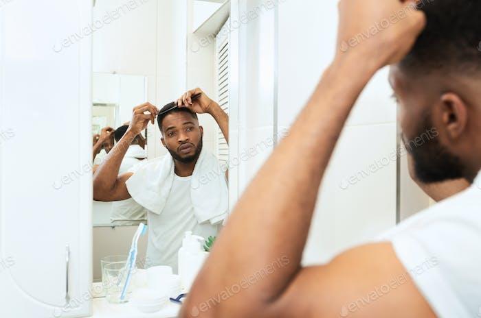 Junge schwarze Mann untersucht seine Haare, Blick auf Badezimmerspiegel