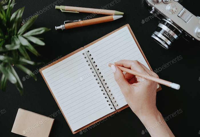 Flat lay female hand writes notes in open notebook