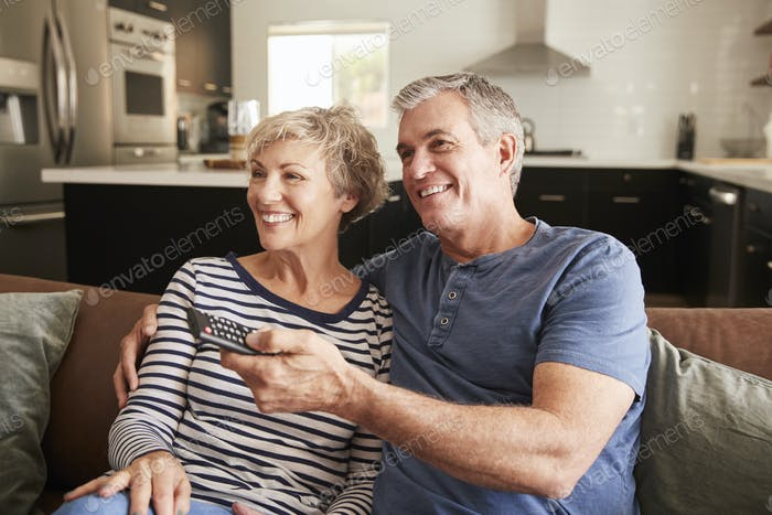 Senior couple sitting on couch watching television, close up