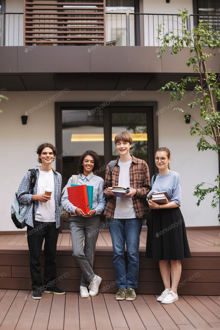 Young smiling students standing with books and folders in hands and happily looking in camera
