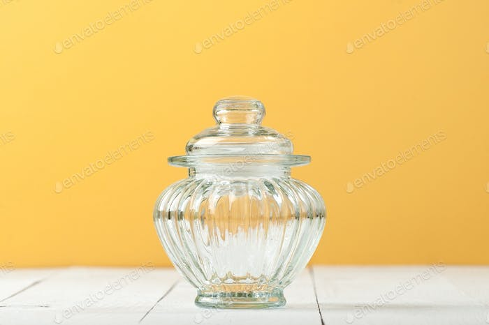 Glass jar with a lid on a white table near the yellow wall.
