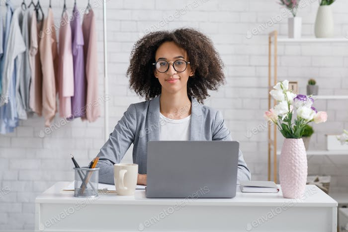 Startup and fashion business. Friendly african american woman in glasses sitting at table with