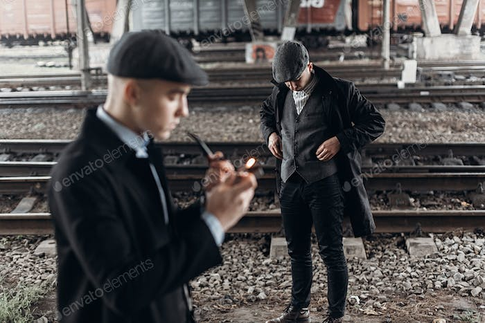 Stylish man in retro outfit, smoking wooden pipe