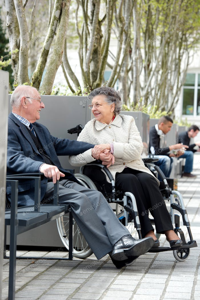 Elderly couple sat outside, woman in wheelchair
