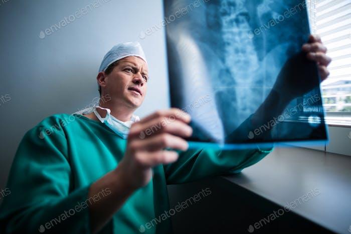 Chirurg sitzt am Fenster und Überprüfung Röntgen