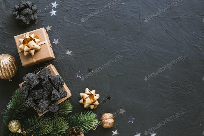 Weihnachtsgeschenke auf schwarzem Hintergrund. Weihnachten Hintergrund mit Tanne, Girlanden, Geschenke.