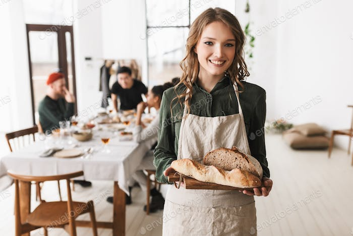Young cheerful woman with wavy hair in white apron holding bread on board in hands