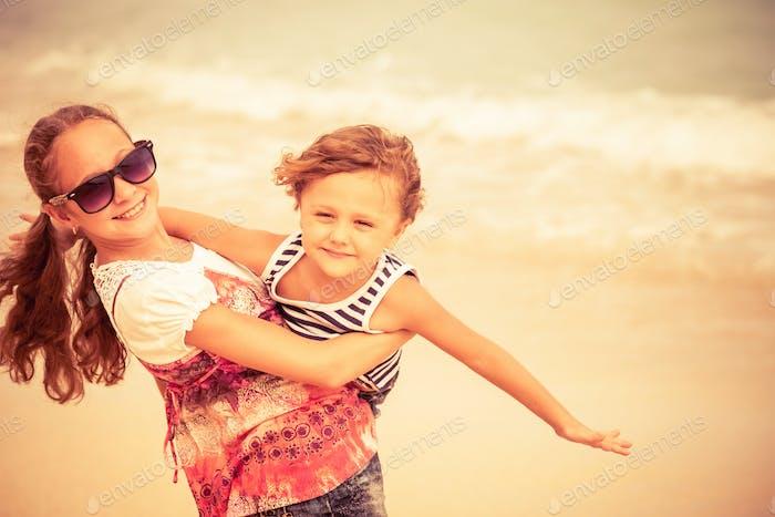 Schwester und Bruder spielen am Strand am Tag Zeit.