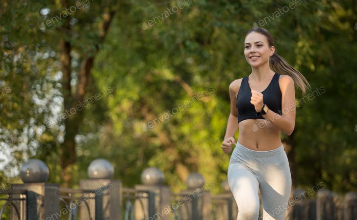 Cute young woman jogging in park, free space