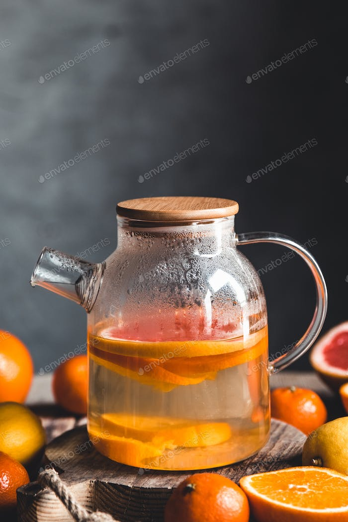 Citrus tea in a transparent teapot on a table with grapefruit and on a wooden table. Healthy drink