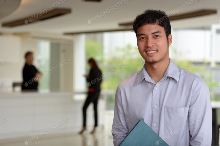 Young Asian businessman inside the office building