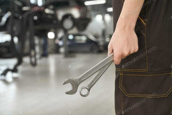Hand of mechanic holding wrenches close up