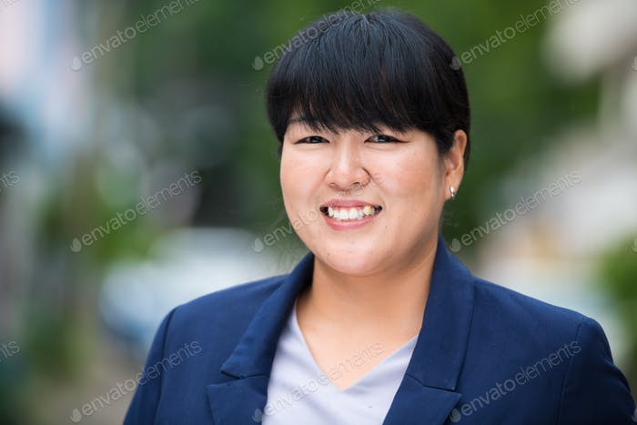 Portrait of beautiful overweight Asian businesswoman smiling outdoors