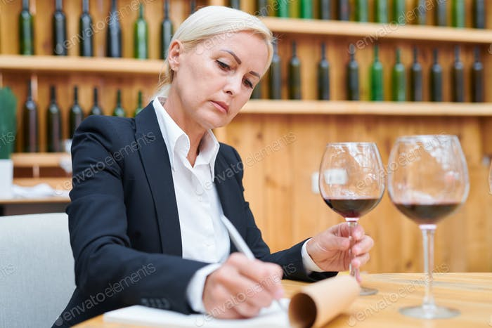 Experienced winery expert making notes about characteristics of red wine