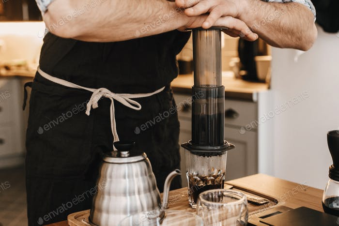 Professional barista preparing coffee in aeropress, alternative coffee brewing method
