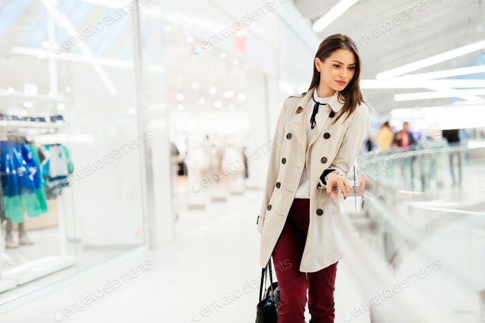Beautiful brunette young woman buying clothes and smiling