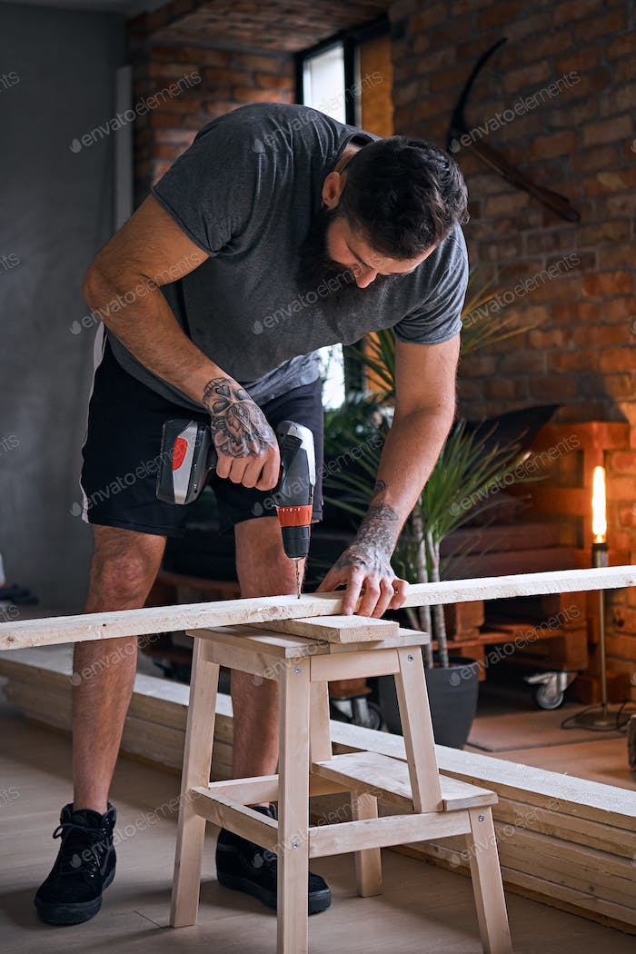 Carpenter drilling a hole in a board in a room with loft interior.