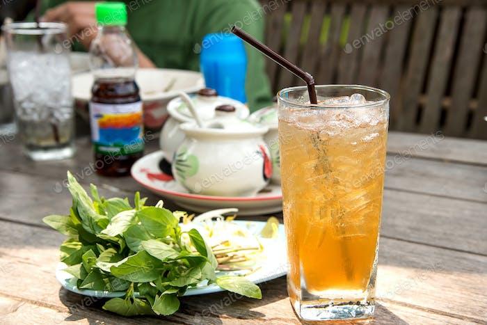 Glas Tamarindensaft mit Eis auf Holztisch
