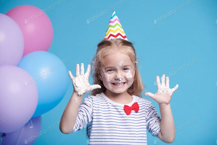 Happy cute little boy in birthday cap showing her palms