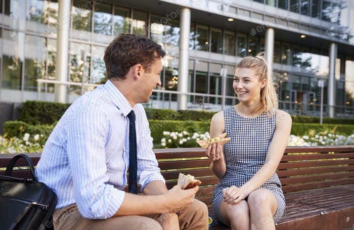 Businessman And Businesswoman Eating Lunch Outside Office