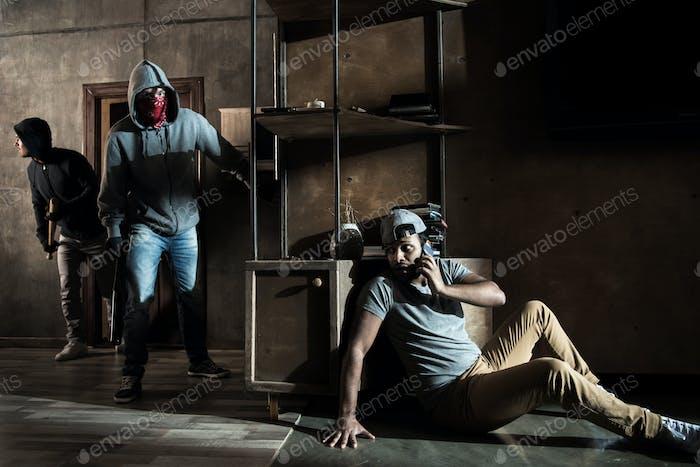 Scared man hiding from burglars breaking indoors, house robbery scene