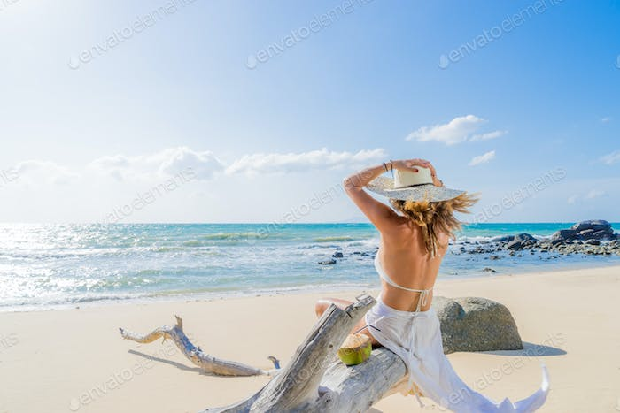 Woman sitting on a tree at the beach
