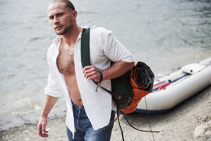 A young man is traveling with a backpack using a boat. The way of life of travel and nature with